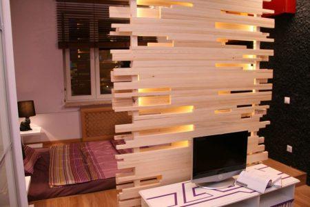 Зонирование спальни-гостиной с помощью декоративной деревянной перегородки
