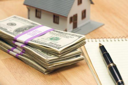 Долларовые купюры, ручки, макет дома