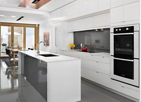 Кухня белого цвета с островом и встроенной техникой